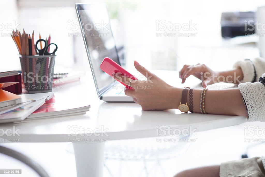 Women who are using the smartphone and laptop in office stock photo