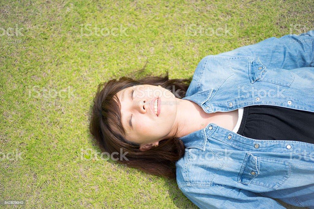 Femmes qui peuvent dormir confortablement improbable sur la pelouse photo libre de droits