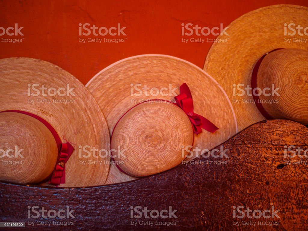Women wicker hats with red lace on a bench, red wall at the background stock photo