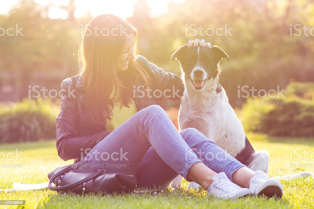 Women with a black and white dog sitting on the lawn outside stock photo