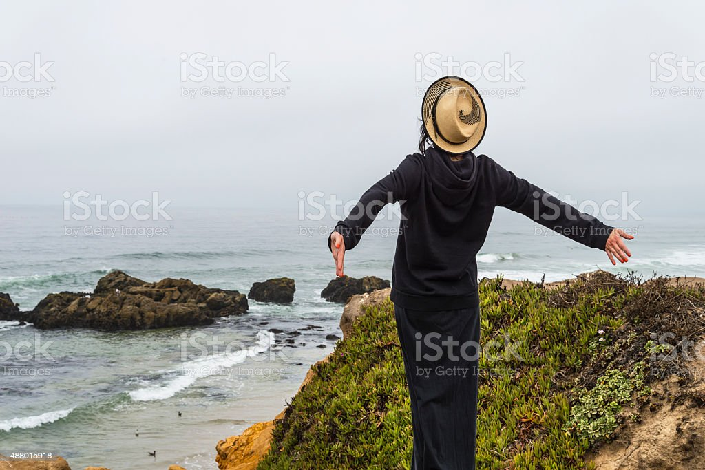 Women with Arms Open on Pacific Coast in California. stock photo