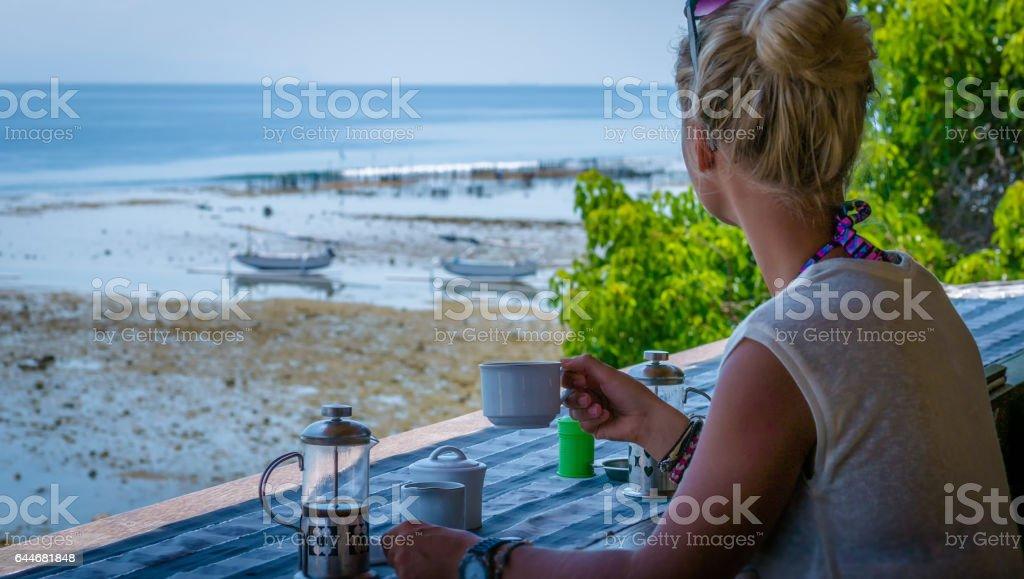 Women with Coffee Cup near Seaweed Algal Plantations - Nusa Penida, Bali stock photo