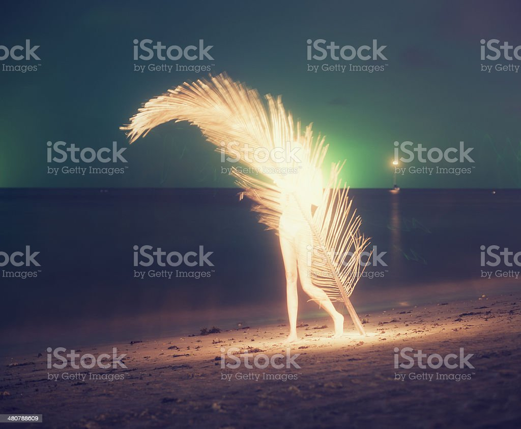 women with giant palm leaf at night stock photo