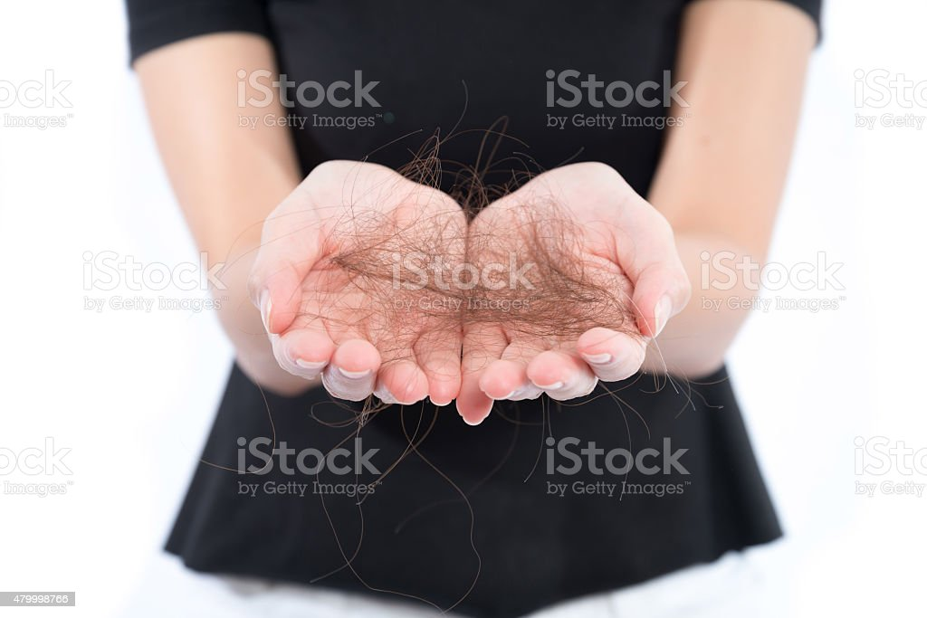 women with hair problem holding loss hair in hand, isloated stock photo
