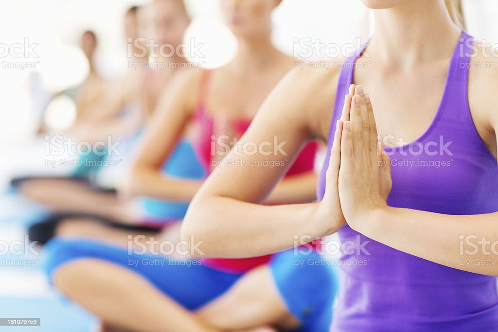 Women With Hands Clasped Doing Yoga In Gym stock photo