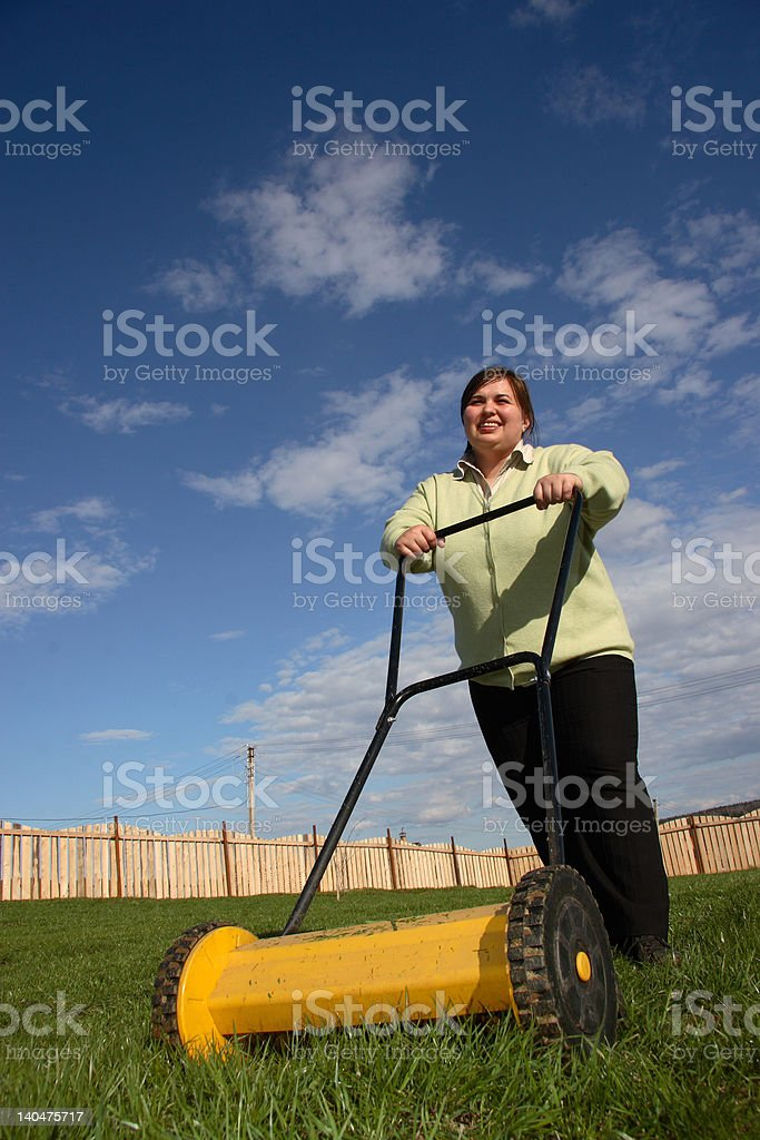 Women with lawn-mower on green grass stock photo