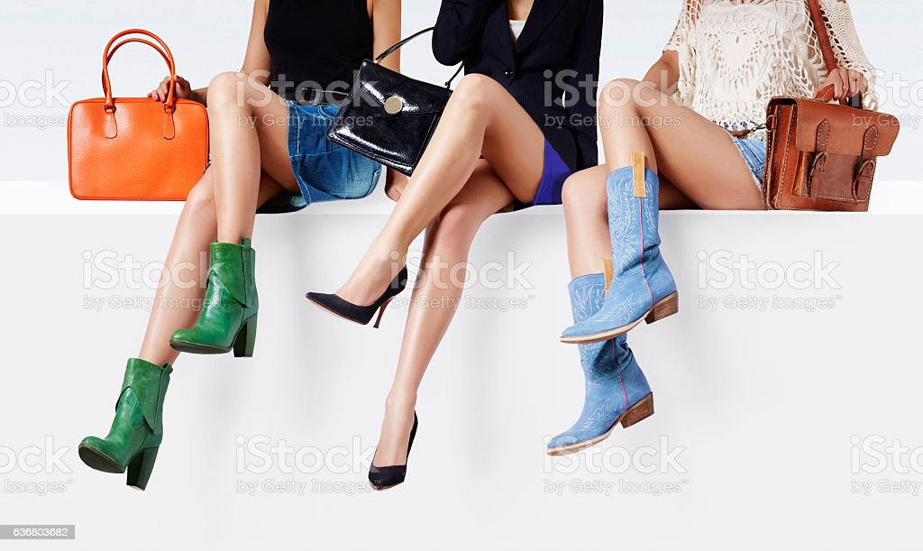 Women with many colorful shoes sitting together. stock photo