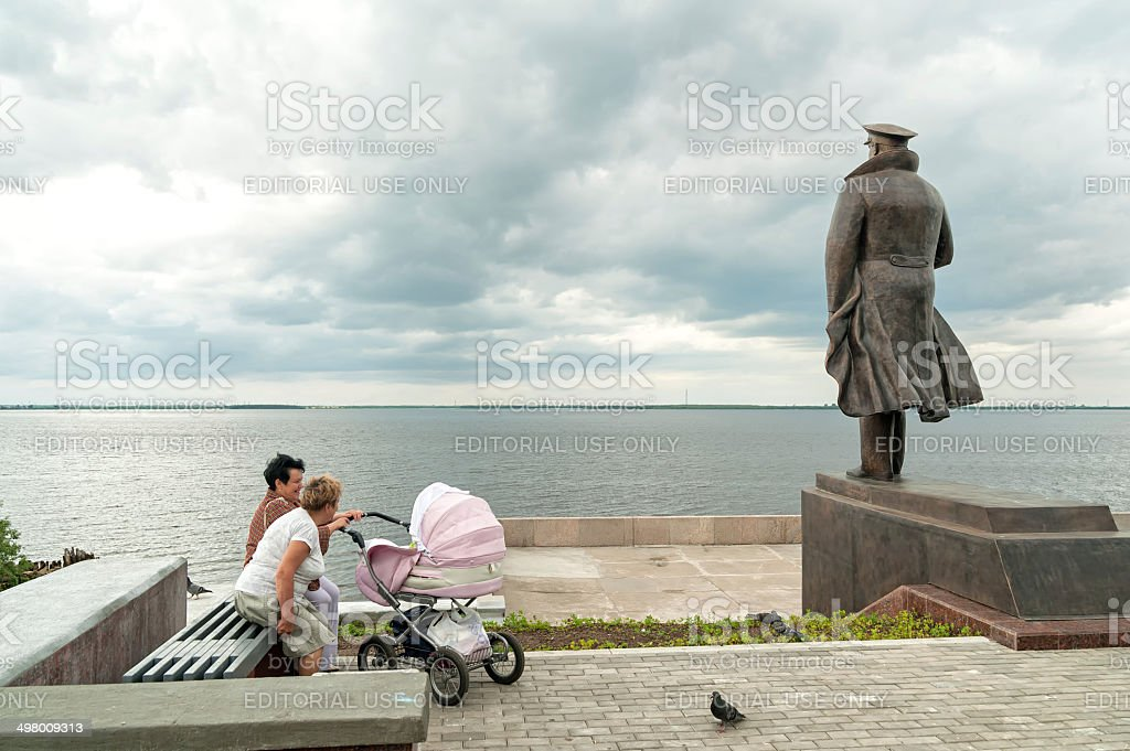 Women with pram sit near monument against river background stock photo