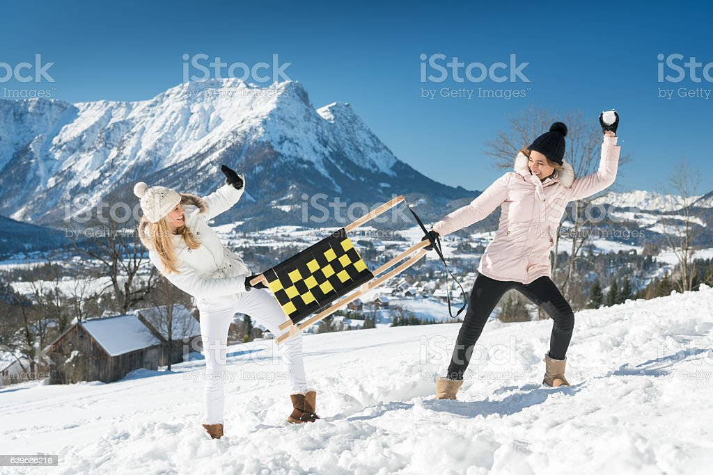 Women with sled in a Snowball Fight, Austrian Alps Panorama stock photo