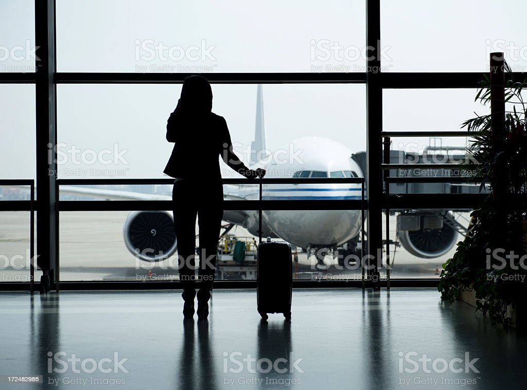 A women with suitcase waiting to load a plane royalty-free stock photo