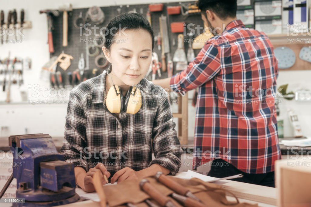 Women working at woodworking project stock photo