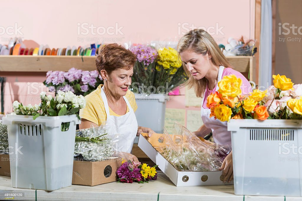 Women working in flower shop with shipment of supplies stock photo