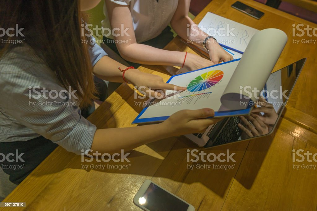 Women working late together, reading report, teamwork stock photo