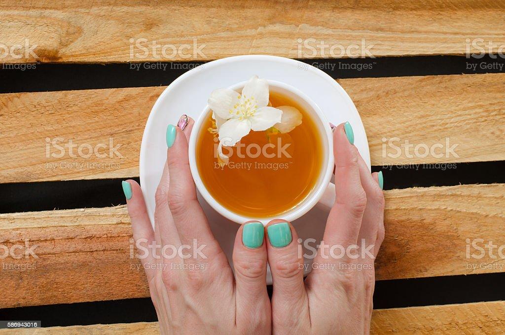 Women's arms around a mug of jasmine tea stock photo