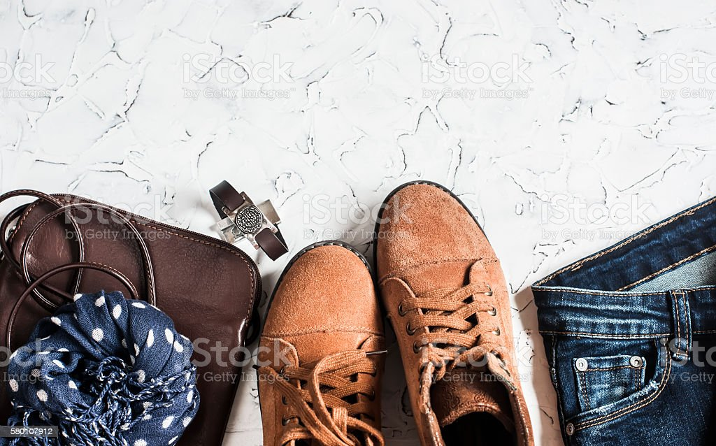Women's clothing and accessories - boots, jeans, leather bag, scarf stock photo