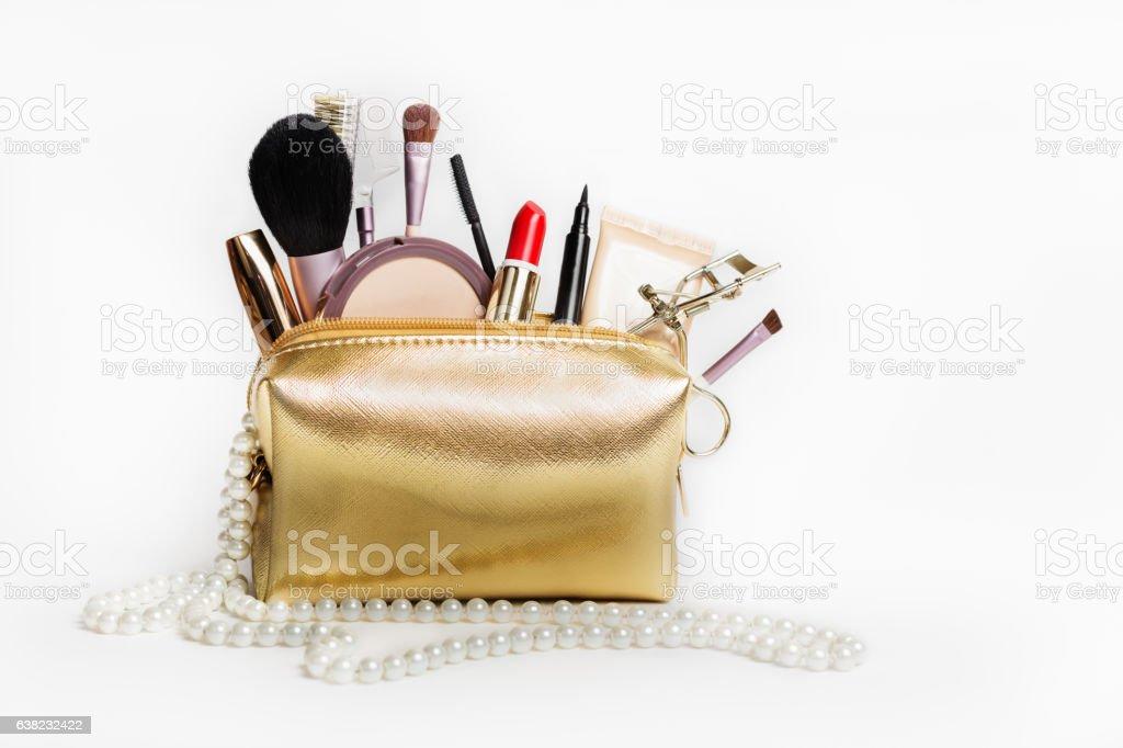Women's cosmetics. Gold cosmetic bag stock photo