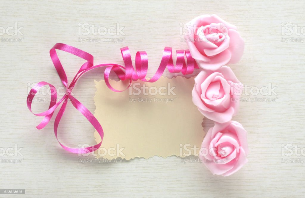 Women's Day card, pink ribbon, rose and paper blank stock photo