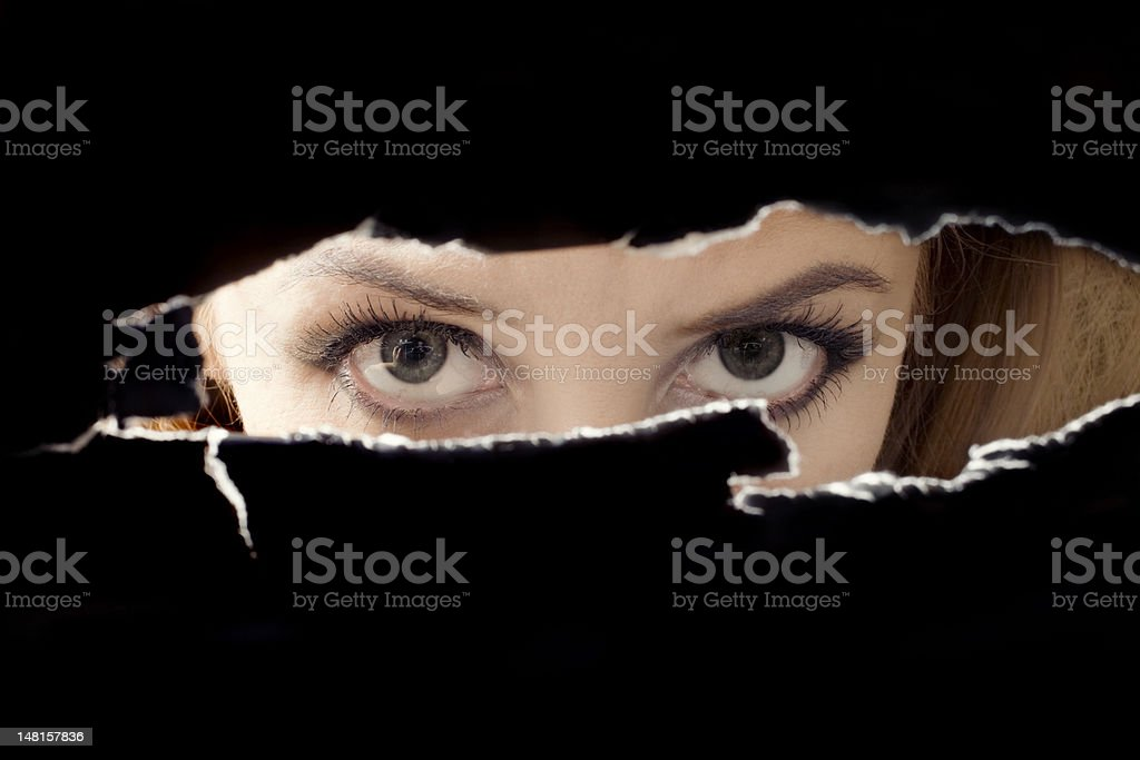Women's eyes spying through a hole stock photo