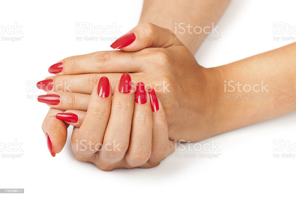 Women's hand clasped together showing off red manicure stock photo