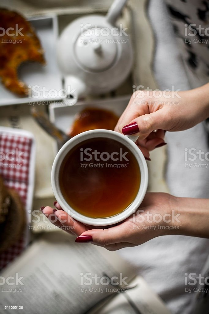 Women's hand holding a warm cup stock photo