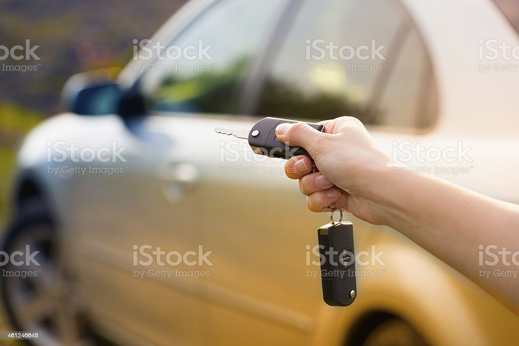 women's hand presses on the remote control car alarm stock photo