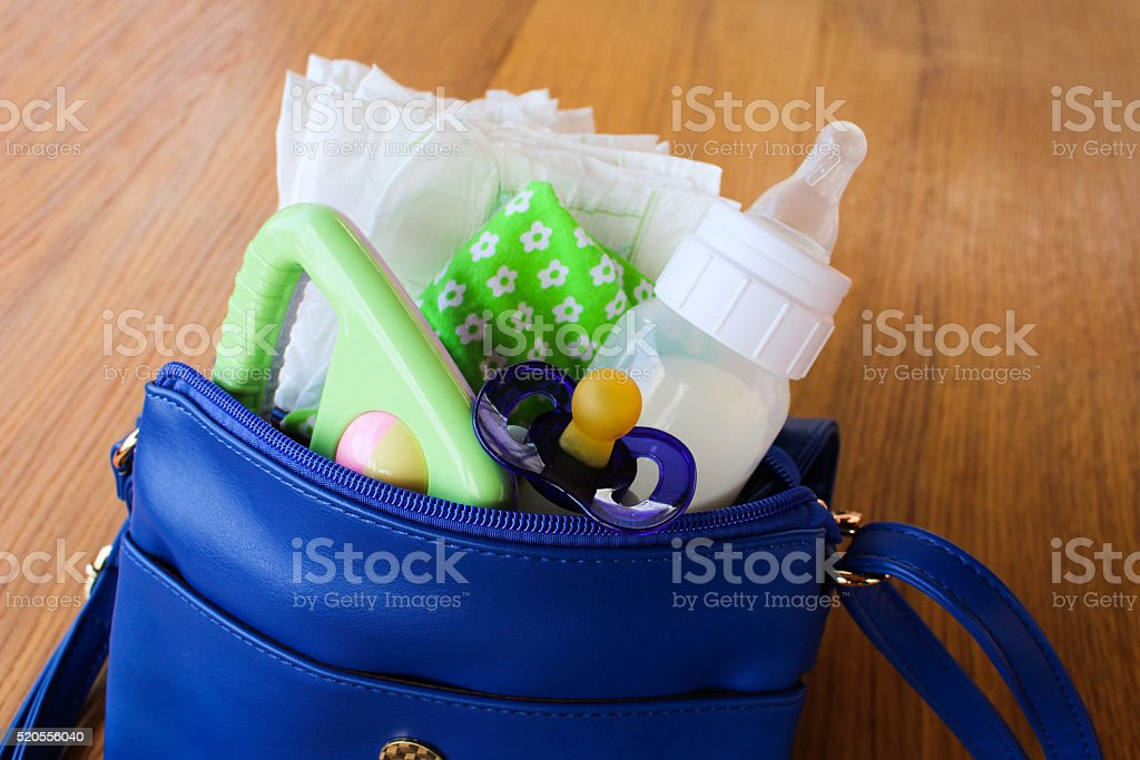 Women's handbag with items to care for the child stock photo