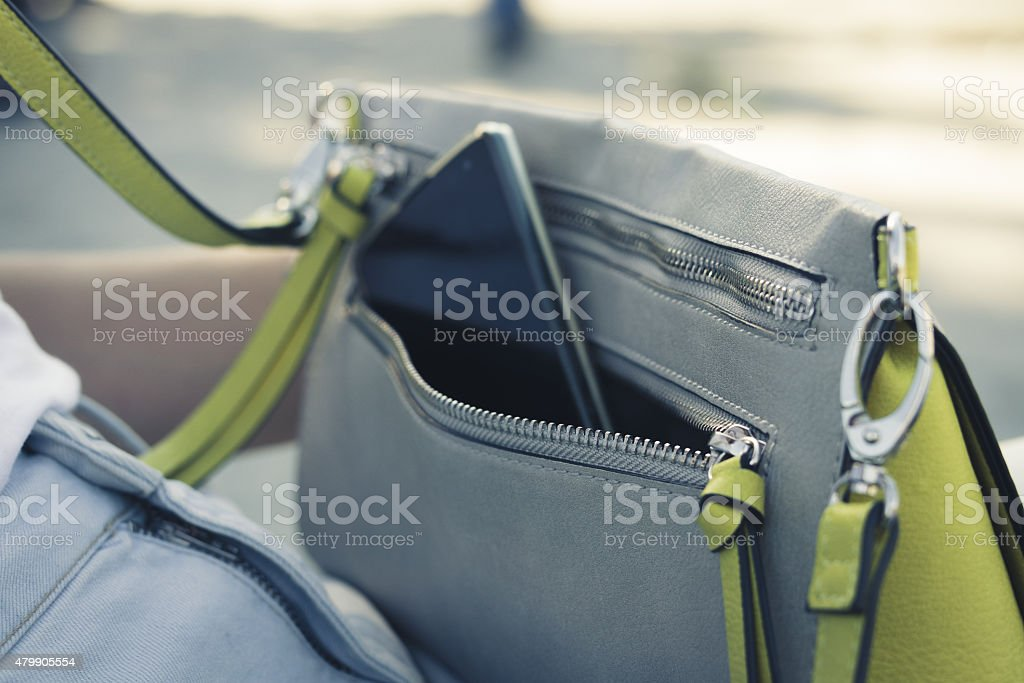 Women's handbag with the phone on the street close up stock photo