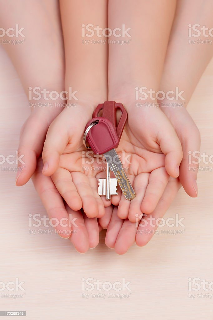 women's hands and arms of the child hold the keys stock photo