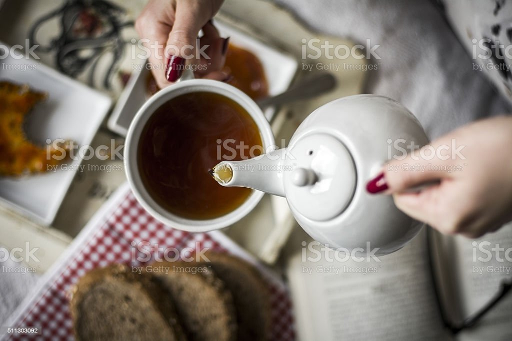 Women's hands pour hot drinks in the cup stock photo