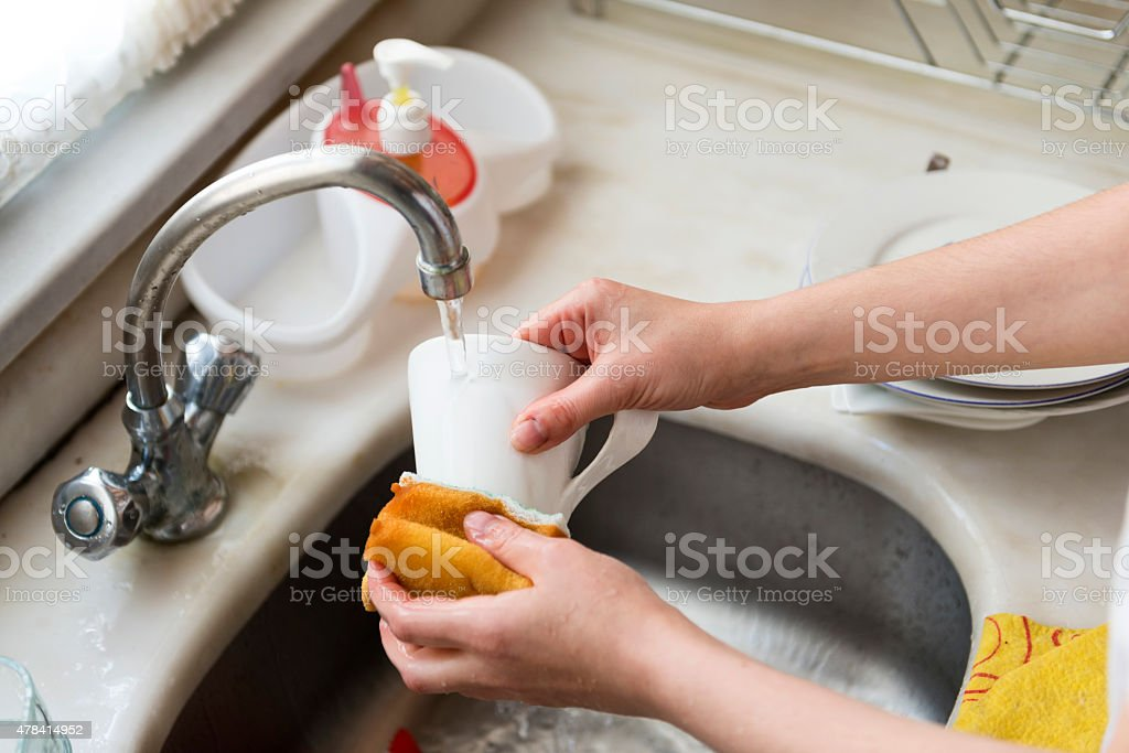 Women's hands washing the dishes stock photo