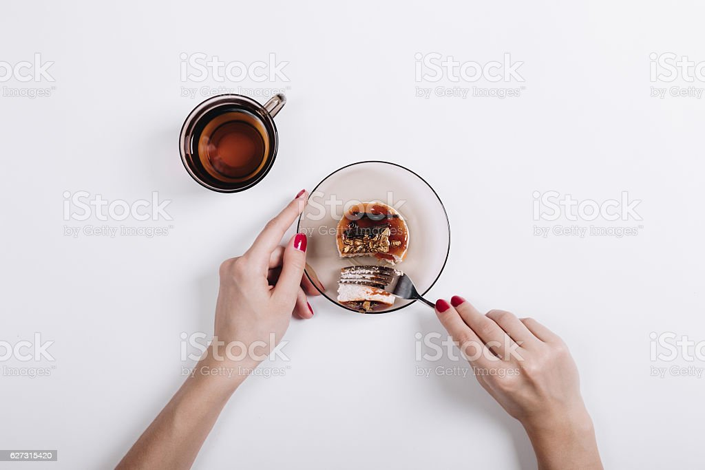 Women's hands with a red manicure cut a cake stock photo