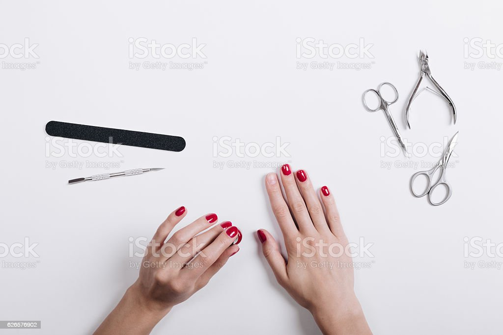Women's hands with a red manicure scissors and nail file stock photo