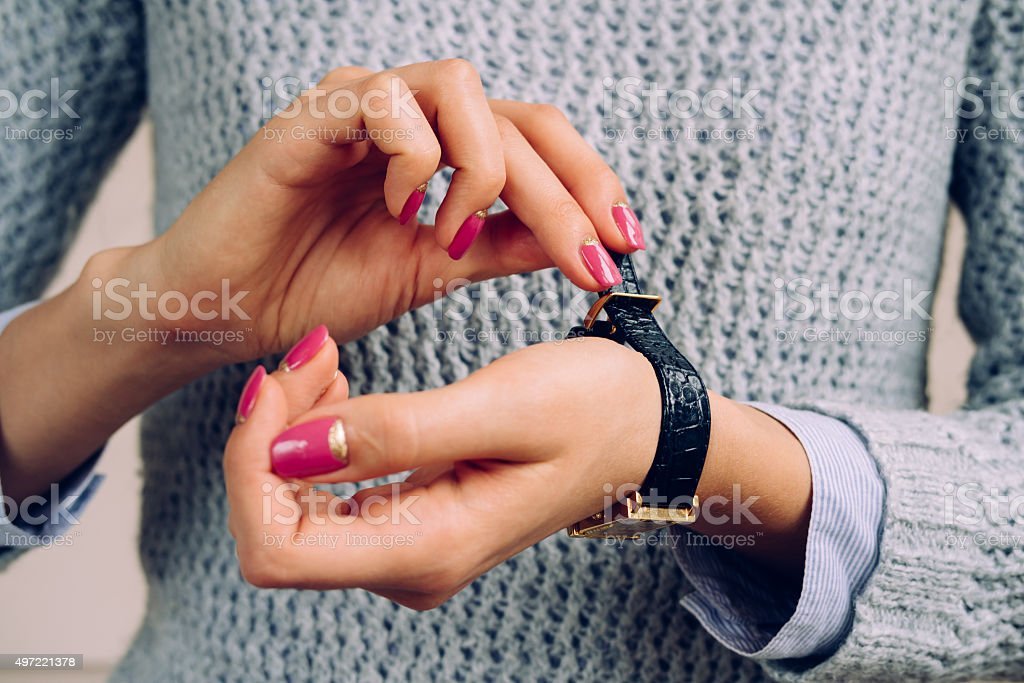 Women's hands with bright manicure fastens the strap on  watch stock photo
