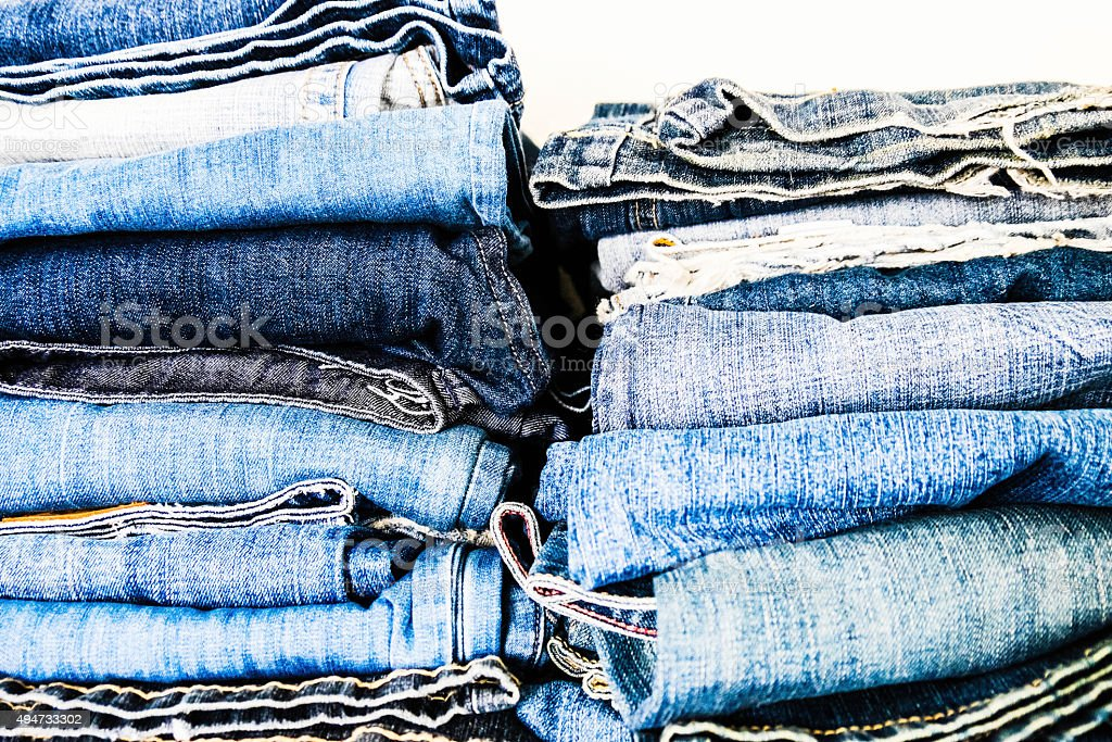 Women's jeans folded in stack in closet or store stock photo