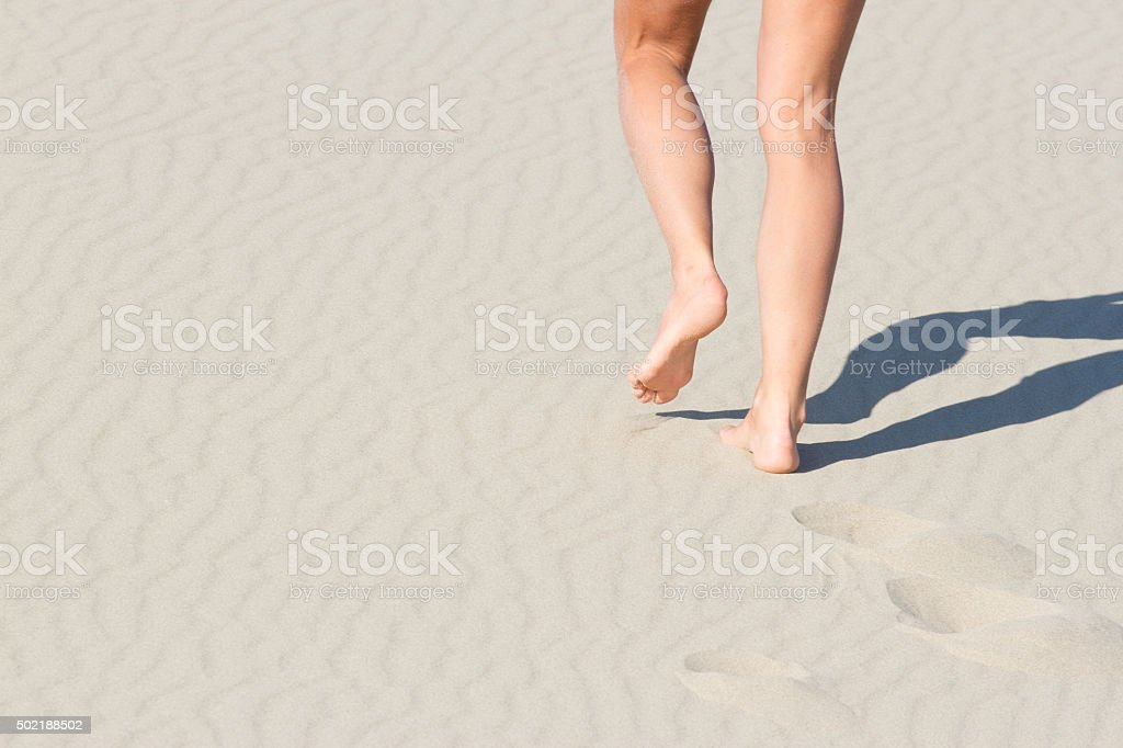 Women's legs from behind. Recreation. Blue sea stock photo