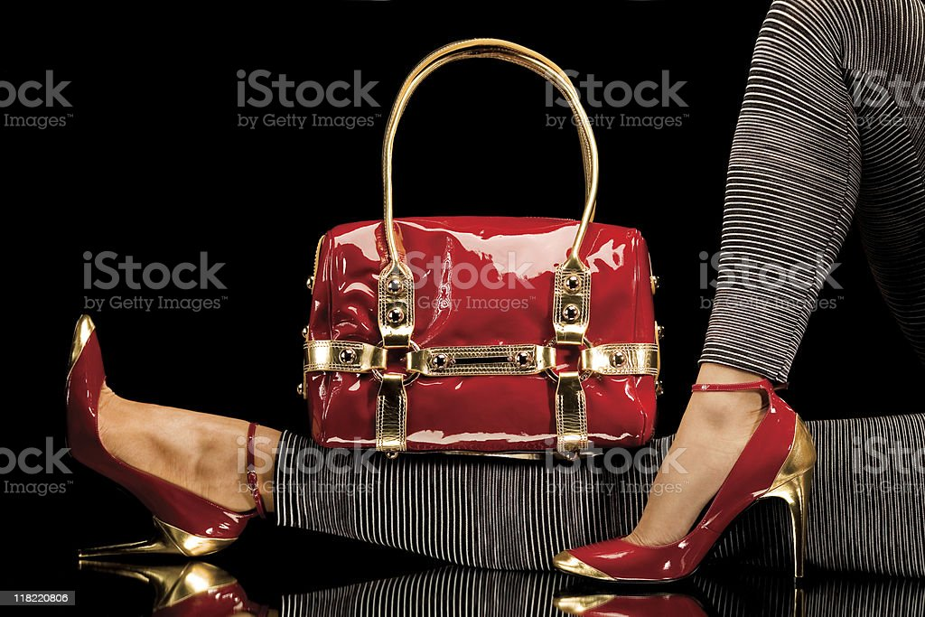 Women's legs with red high heels and red purse stock photo