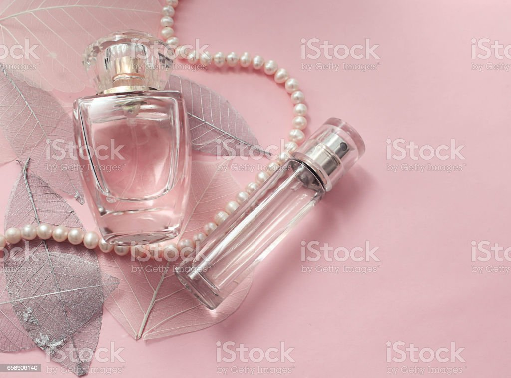 Women\'s perfume on a pink background with a pearl necklace and...