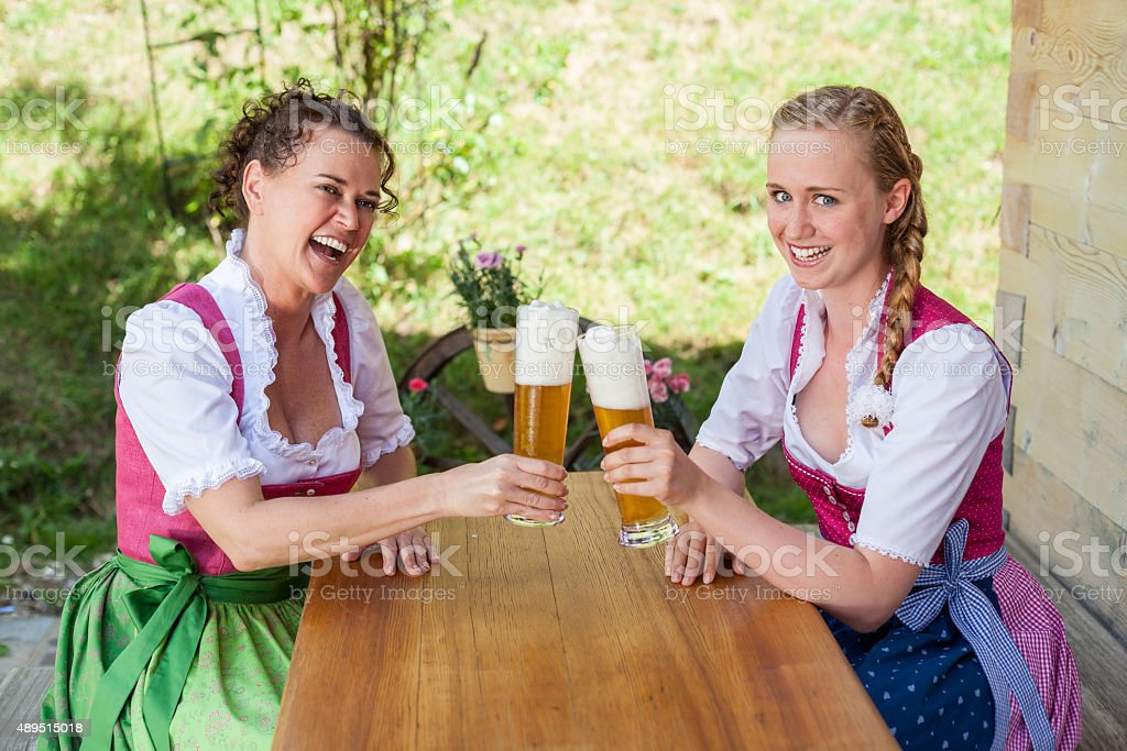 women´s sitting in dirndl in front of a glass beer. stock photo