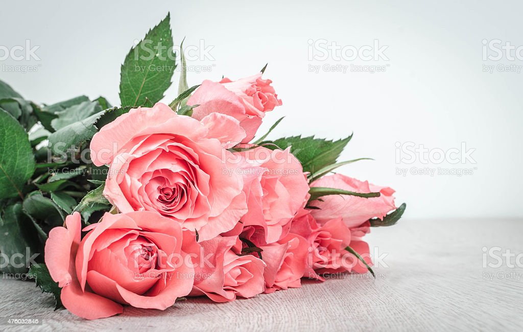 Wonderful pink roses on wooden table stock photo
