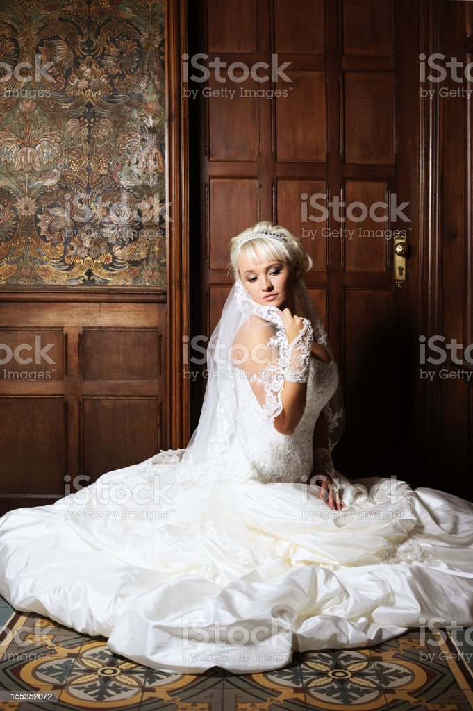 Wonderful White Bride sitting on Floor before Antique Wall royalty-free stock photo