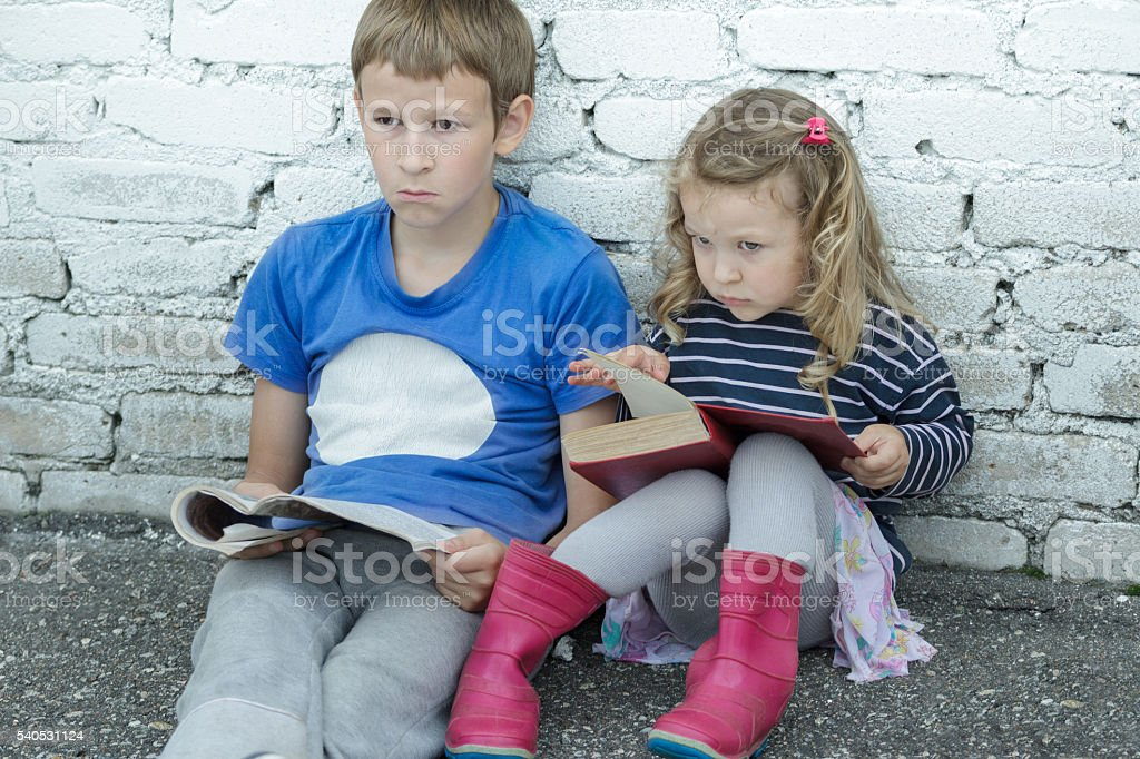 Wondering sibling children sitting on asphalt ground with books stock photo