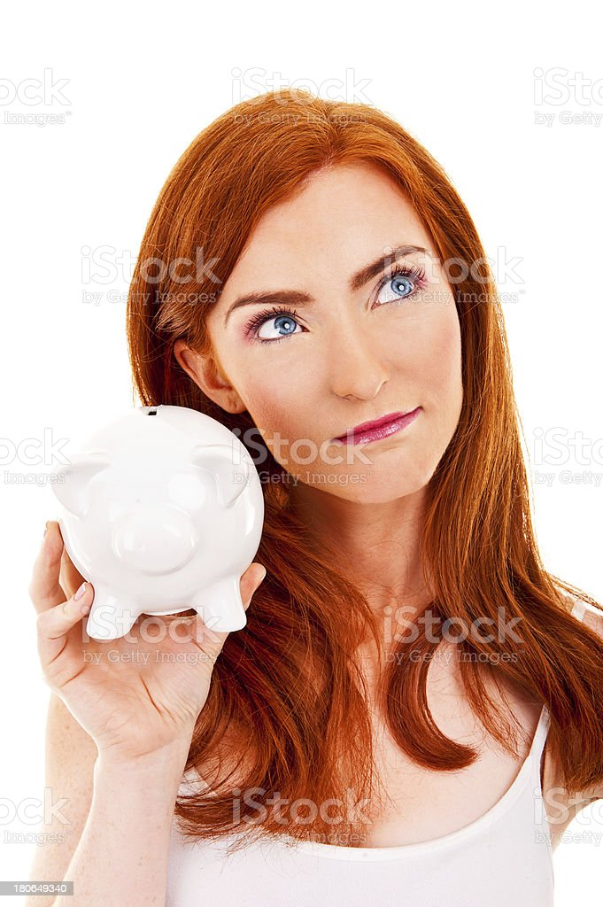 Wondering woman with piggybank in her hand over white background royalty-free stock photo