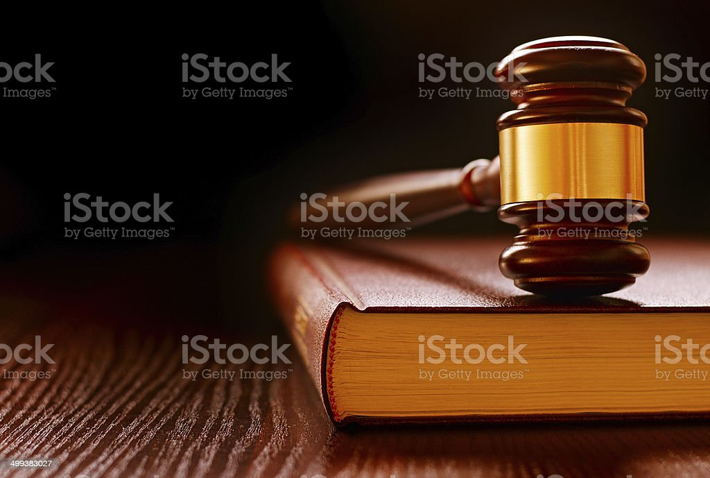Wood and brass judges gavel on a law book stock photo
