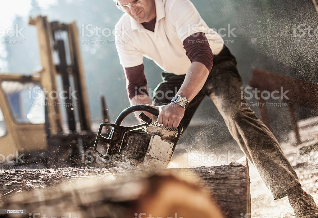 Wood artist working processing timber with chainsaw stock photo