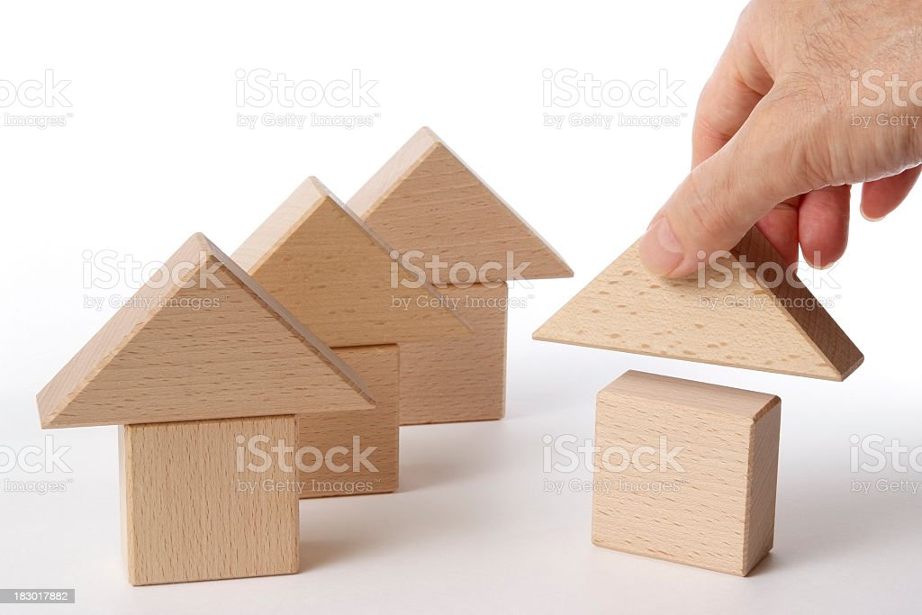 Wood block house with hand on white background royalty-free stock photo
