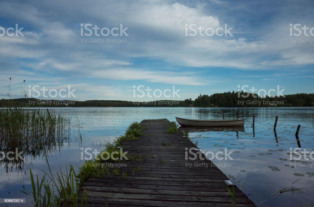Wood Bridge and Boat At Swedish Lake stock photo