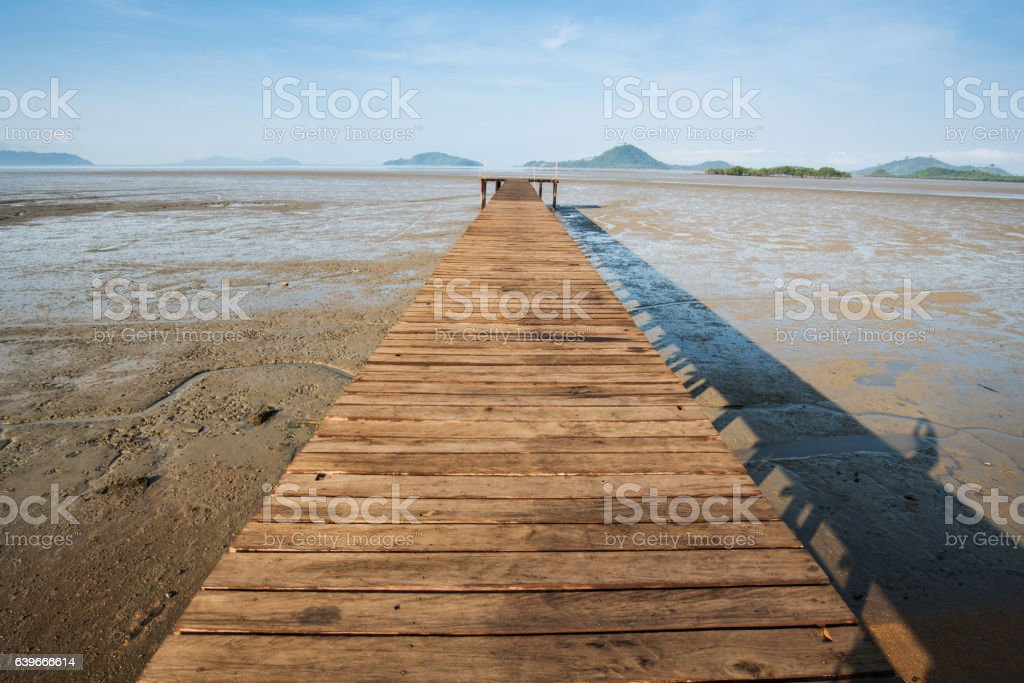 Wood bridge over land extends into the sea stock photo