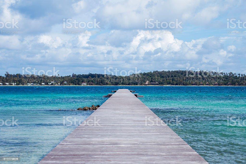 Wood bridge to the sea stock photo
