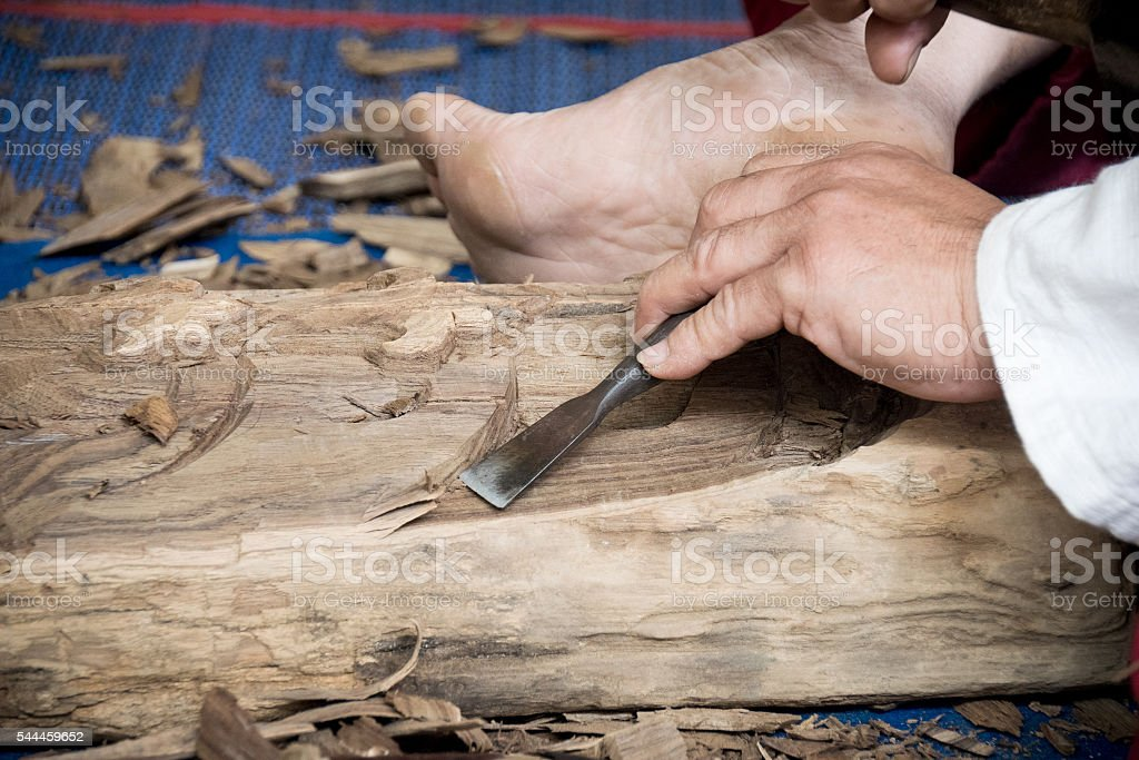 Wood carver man is using a wood chisel to extract. stock photo