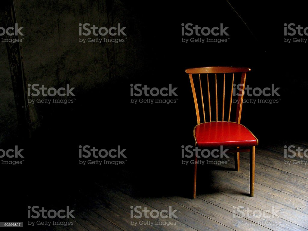 Wood chair with red seat in dark room with wood floor stock photo